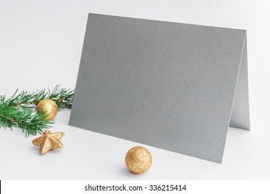 Mockup. Silver card, golden Christmas balls and pine branch on a white background.