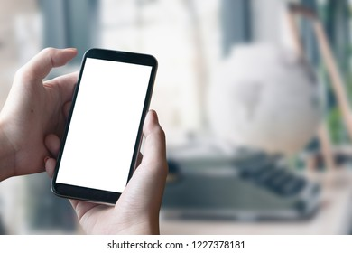 Mockup smartphone blank screen in woman hands over blurred background.