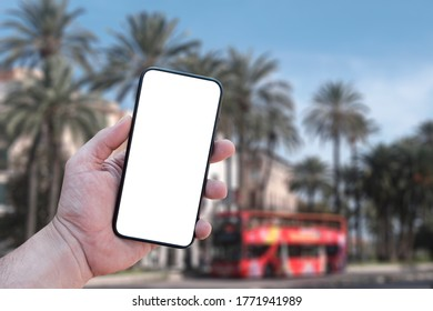 Mockup of the smartphone in the man hand, with a white screen on the background of a tourist bus and palm trees. Tourism and travel online