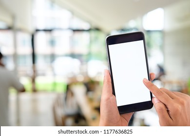 Mockup smartphone on female hands empty display on blur office background.