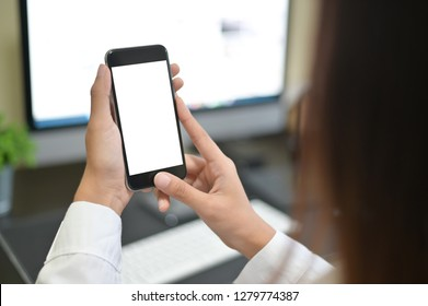 Mockup smartphone on female hands empty display on office table with blur background. - Image