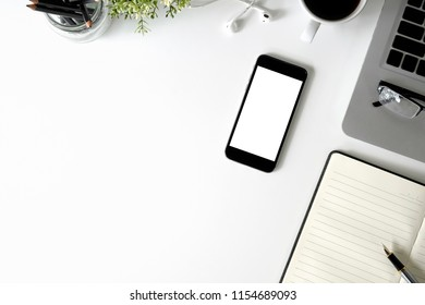 Mockup smartphone on office desk with laptop and notebook paper, Copy space mockup mobile phone with top view.