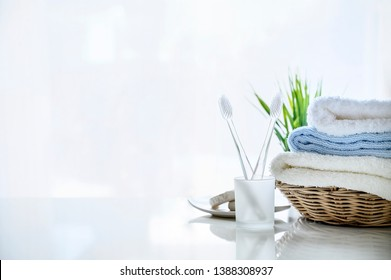 Mockup soft towels in basket and toothbrush on white background, copy space for product display.