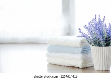 Mockup stack of white towels and houseplant on white table with copy space.