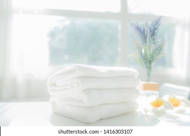 Mockup stack of white towels and houseplant on white table with copy space