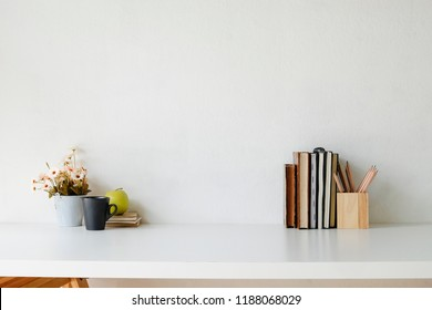 Mockup table with flower, cup of coffee, books, green apple and jar of pencil on white table.