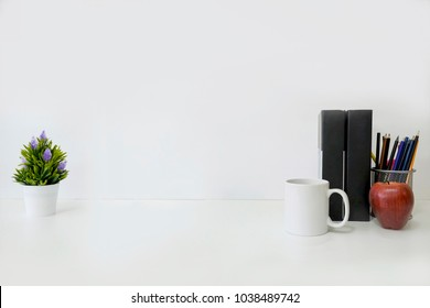 Mockup table with plant decorate, cup of coffee, book,red apple and jar of pencil on white table and white background.