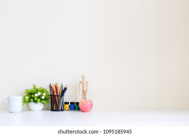 Mockup table with plant decorate, cup of coffee, water colour, jar of colour pencil and wooden model artist workspace. - Shutterstock ID 1095185945