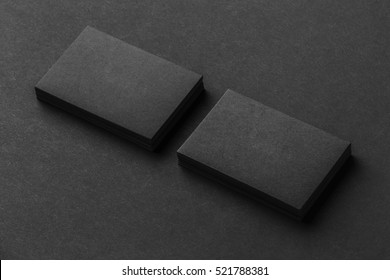 Mockup of two blank business cards stacks at black textured background.