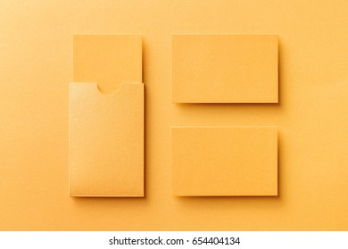 Mockup of two blank business cards and a cardholder at golden color textured paper background.