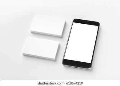 Mockup of two blank horizontal business cards and black cell-phone at white textured paper background.