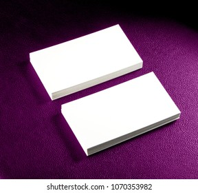 Mockup of two horizontal business cards at purple leather background