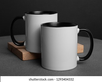 Mock-up two white cups on a black and concrete background
