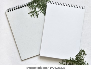 mockup from a two white sketchbooks on a spring lying on a linen tablecloth with sprigs of green thuja