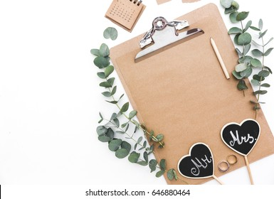 Mockup wedding planner flat lay. Accessory on the table.White background, still life. Events and party desktop. Feminine scene. Workspace with paperboard, wedding decorations and eucalyptus branches.