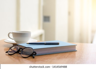 Mockup white cup of coffee, text book or diary,glasses and pen design template isolated on wooden desk at modern home office. Meeting,reading or examination time concept.