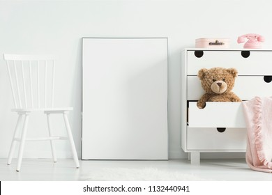 Mockup of white empty poster between chair and cabinet with teddy bear in kid's room interior. Real photo. Paste your poster here