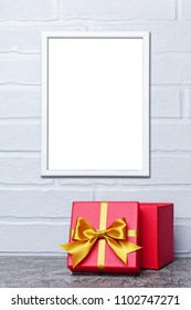 Mock-up of white frame with copy space for poster and red classic gift box with golden satin bow on gray concrete and brick wall background