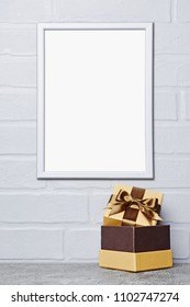 Mock-up of white frame with copy space for poster and golden classic gift box with brown satin bow on gray concrete and brick wall background