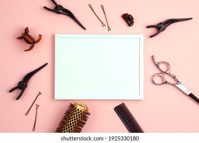 Mockup white frame of professional hair cutting shears comb for separating hair hairpins section hair clips and gold round hair brush for styling with copy space on pink. Hairdresser salon equipment