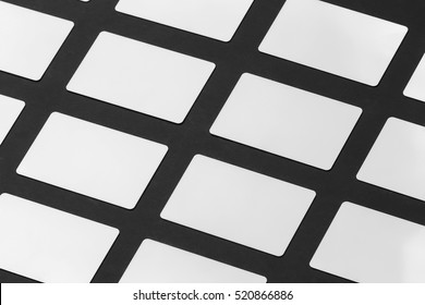 Mockup of white gift plastic cards arranged in rows at black paper background.