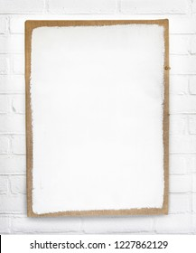 Mockup of white grunge empty canvas photo frame with brown border hanging on white brick wall with space for own text