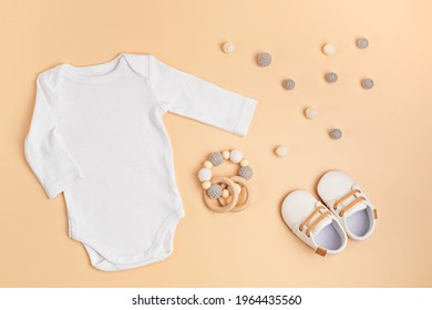 Mockup of white infant bodysuit made of organic cotton with eco friendly baby accessories. Onesie template for brand, logo, advertising. Flat lay, top view