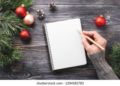 Mockup with white paper notebook and Christmas decorations on wooden table. Woman's hand writing in notepad. Top view.