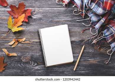Mockup with white paper notebook decorated autumn leaves and checkered scarf on wooden table. Top view.