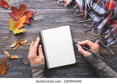 Mockup with white paper notebook decorated autumn leaves and checkered scarf on wooden table. Woman's hand writing in notepad. Top view.
