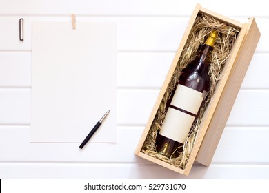Mockup. White sheet and bottle of alcohol in a box on a white table.