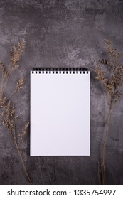Mockup of white wire notebook on dark grey textured background with dry flower, Ideals for presentation and design artwork