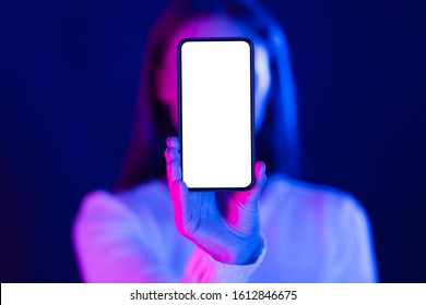 Mockup. Woman showing blank smartphone screen in studio with blue and pink neon lights, free space
