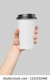 Mockup of women's hand holding white paper large size cup with black cover isolated on grey background