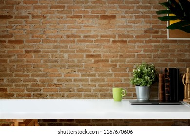 Mockup workspace vintage books, dry flower, office stationery and cork frame over red brick wall.
