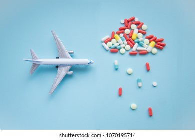model airplane with multicolored pills from motion sickness close-up on a blue background. concept illness in travel