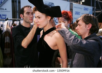 A model is being prepared at the backstage area of a fashion show.