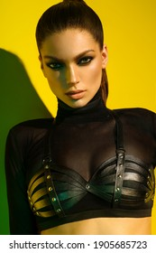 Model in black clothes with leather harness on yellow background in studio