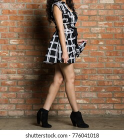Model in a Black and White Pattern Dress with a Brick Wall