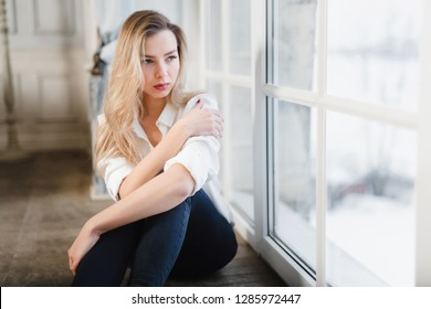 Model blonde white shirt blue pants jeans sitting on wooden parquet floor by window looking thoughtfully sad pleasantly comfortable legs crossed. Copy space.