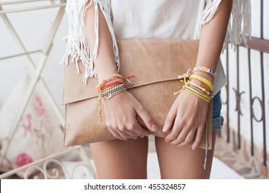 Model with bracelets holding a purse