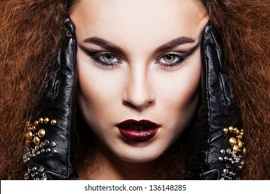 Model with bright make-up, dark lips, lush red hairs. black leather gloves