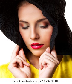 model with bright makeup, wearing a black hat, against white background