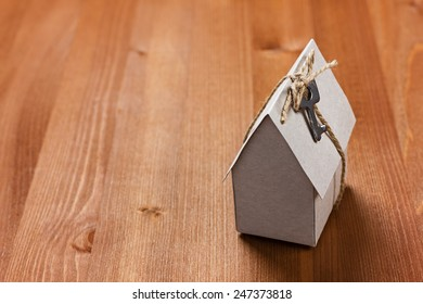 model of cardboard house with a bow of twine and key. building, loan, real estate or buying a new home concept.