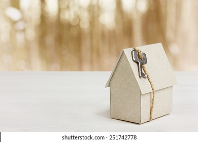 model of cardboard house with key against bokeh background. building, loan, real estate or buying a new home concept.