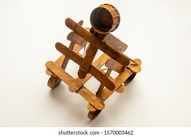 Model of a catapult made out of ice lolly sticks and plastic tops isolated on a white background