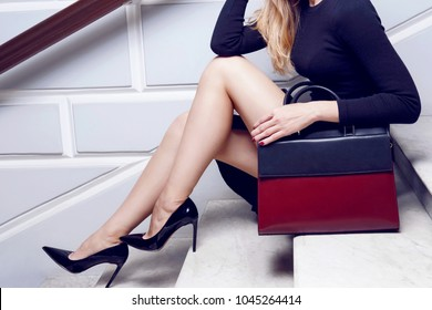 Model close up legs in high heel with big leather red bag sit on the white stair. Fashionable classic outfit