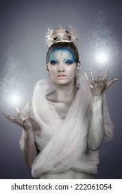 Model with creative make up and body painting posing as Ice Queen or Winter Fairy