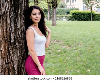 Model (Dilan) posing during phot​oshoot ​in Milan, Italy. Wearing pink pants and white top, with curly brown hair.