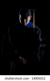 Model in doctoral / masters graduation robes and regalia in a low key image looking solemn